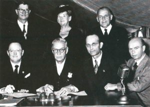 Seated at the table are signers of the amalgamation agreement: J. H. Walker Sr.; F. J. M. Beetge, moderator of the Full Gospel Church; H. L. Chesser; and H. R. Carter, secretary general of the Full Gospel Church. Witnessing the ceremony are J. H. Saayman, Mrs. Saayman, and A. H. Cooper