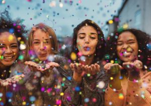 girls blowing confetti